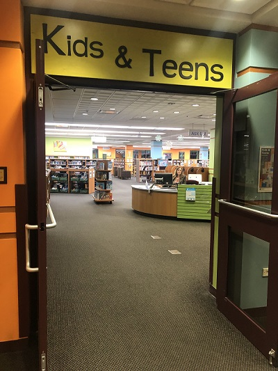 Entrance to the Kids & Teens department, through which you can see staff sitting at the help desk.